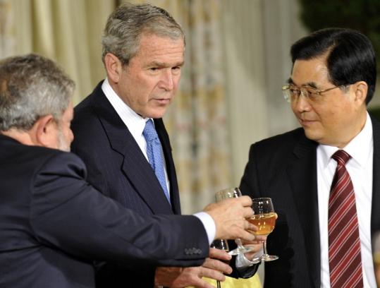 President Hu Jintao of China (right) shared a toast with President Bush and President Luiz Inacio Lula da Silva of Brazil in Washington Friday but left the economic summit without responding to appeals to use China's reserves to aid an IMF bailout effort.