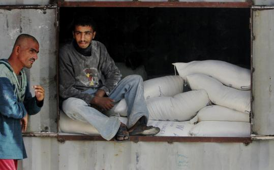 A man sat on bags of flour at a warehouse in the Rafah refugee camp, Gaza Strip, yesterday. Israel and Hamas have traded fire for two weeks after nearly five months of relative quiet.