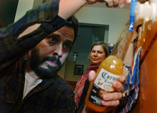 Peter Chipman bottles hard cider made from apples found in East Boston as Giordana Mecagni looks on.