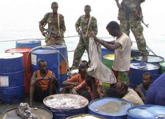 Police guarded suspected Somalian pirates in Bassaso, Somalia, yesterday. Pirates have seized eight ships, including a Saudi Arabian oil tanker, off the Somalian coast in the last two weeks.