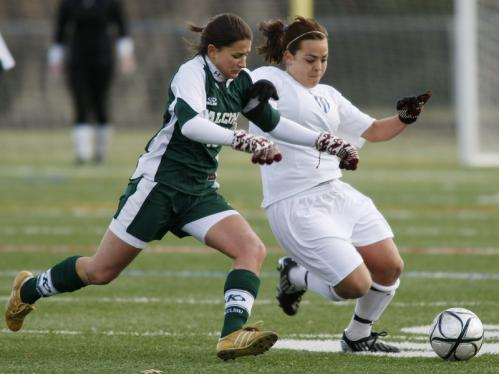 Minnechaug's Joelle Barr battles Acton-Boxboro's Ceci Jensen (right).
