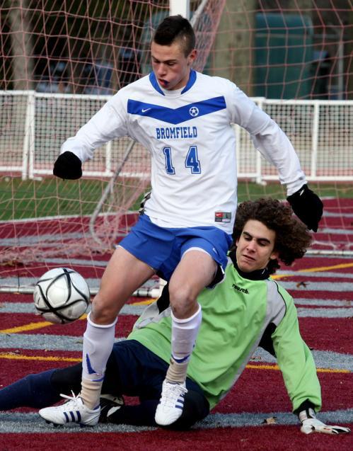 Bromfield's Cody Osgood (14) tries to work the ball past Hamilton-Wenham goalie Jackson McDonald.