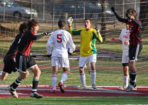 Masconomet goalie Jon Doucette (in yellow) seems to wonder what happened a split second after Mt. Greylock scored its third and winning goal. While Mt. Greylock players (left to right in black and red) Sam Sokolsky-Tifft , Jordon Tuboly and Nick Walker celebrate.
