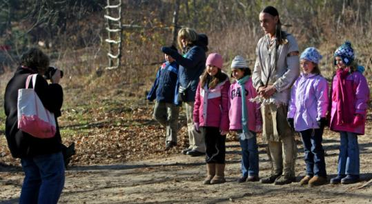Phillip Wynne posed with a group of school children on the Wampanoag Homesite at Plimoth Plantation.