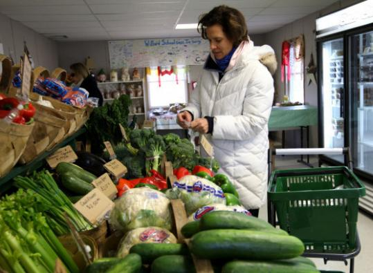At Concord's Verrill Farm, Valerie Eagan of Sudbury buys vegetables at the temporary farm stand, which opened recently.