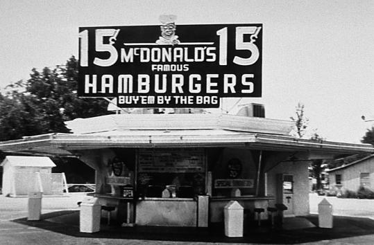 The original McDonald Brothers restaurant in San Bernardino, Calif., in this undated photo. Their slogan ''buy 'em by the bag'' was a more palatable suggestion when hamburgers sold for 15 cents each.