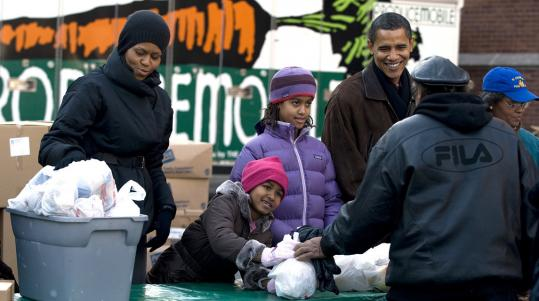 President-elect Barack Obama, with his wife, Michelle, left, and daughters Sasha and Malia, handed out food for Thanksgiving during a visit yesterday to Chicago's St. Columbanus Parish.