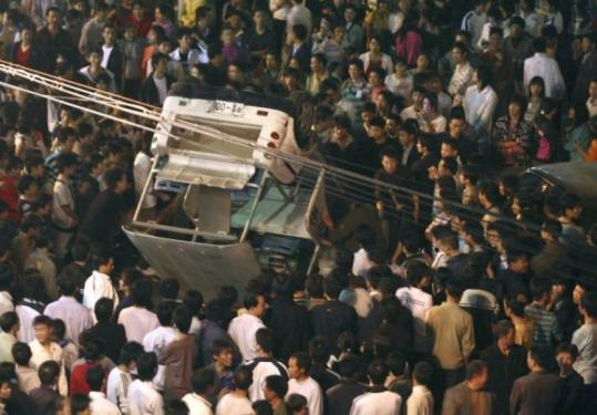 Workers surrounded an overturned police car outside a toy factory in Dongguan, China, on Tuesday.