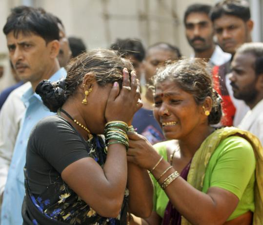 A woman grieved yesterday for her two children while waiting for their bodies in Mumbai.