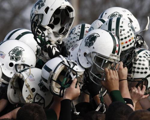 Dartmouth football players raise their helmets in unison before the game.