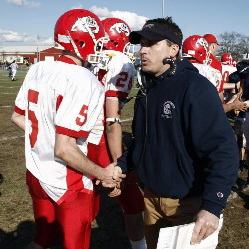 Old Rochester's Alex Goodman (5) is congratulated by Apponequet head football coach Bob Lomp.