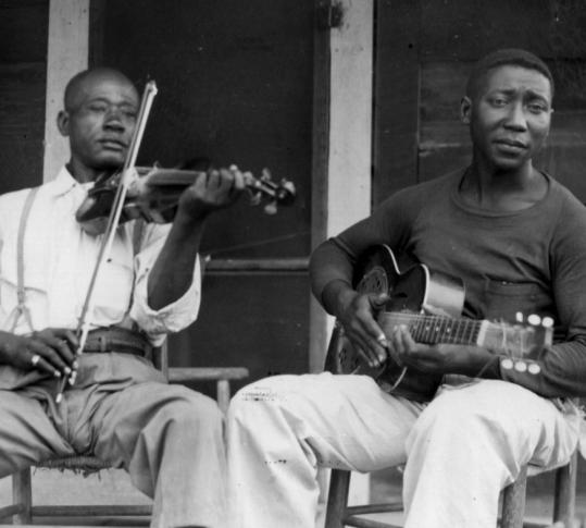 Henry Sims (left) and Muddy Waters, photographed by John Work, 1943.