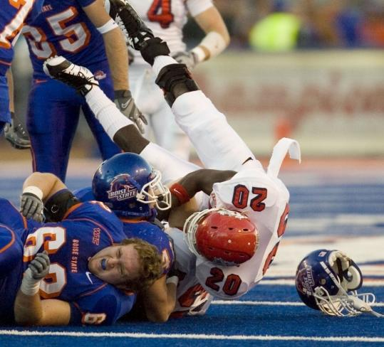Boise State lineman Kevin Sapien lost his helmet but not his head while blocking Ian Johnson.