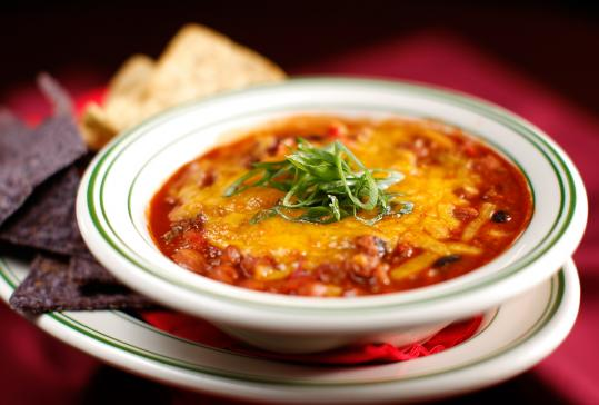 At Roadhouse, chili is packed with plump, tender beans, ground beef, and spices and sprinkled with cheddar, with tortilla chips poking out the sides.