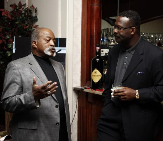Red Sox legend Luis Tiant (left) chats with Patriots Hall of Famer Andre Tippett. Below: Joe and Jen Andruzzi.