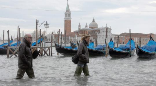 People waded in knee-deep water on a flooded quay of Venice yesterday. City officials said the tide peaked at 61 inches.