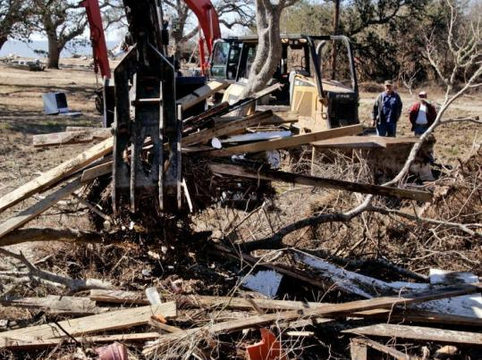 Hurricane debris was scooped recently in Smith Point, Texas. Spotters watch for bodies and hazardous debris in the rubble.