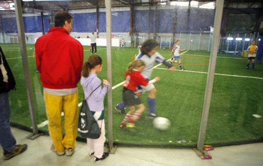 Plexiglass boards provide a clear view of a girls' soccer match at Teamworks in Acton; the company also has an indoor facility in Northborough.