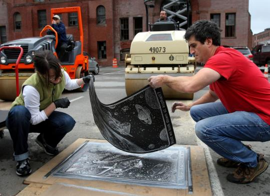 Anne Lucius (left) and James Kraus lift a poster created by an asphalt roller as part of an event designed to promote greater creativity in the design and use of asphalt spaces.