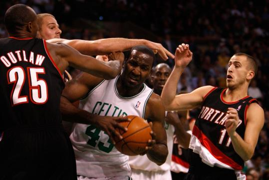 Celtics center Kendrick Perkins is at a decided disadvantage in the arms department, but he has the one thing his Trail Blazers adversaries don't - the ball - as he grabs a first-half rebound.
