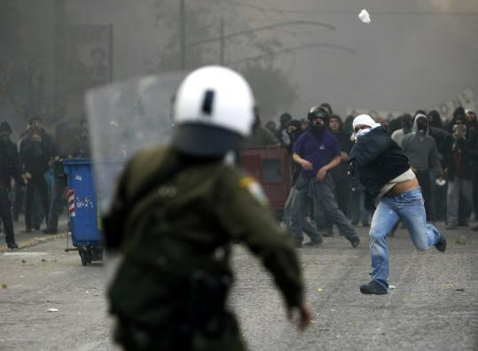 A protester threw a stone at police during a violent demonstration in Athens yesterday. Riots broke out in Athens and Thessaloniki after police fatally shot a 15-year-old in the capital.