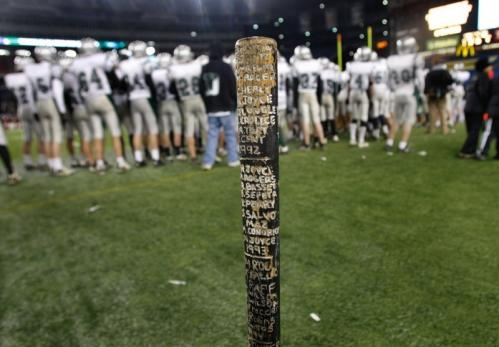 Names of former Duxbury players are carved into a sledgehammer on the Duxbury sidelines.