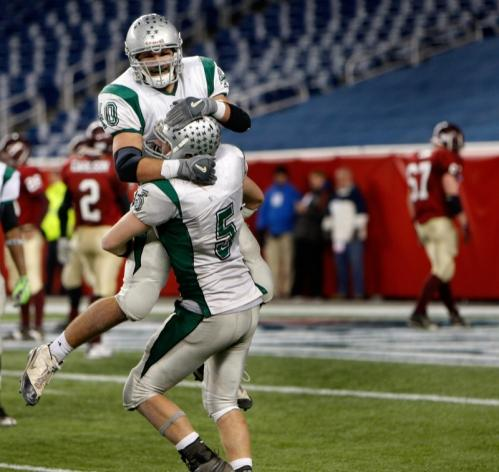 Duxbury's Kyle Gavoni gets a celebratory ride courtesy of Shane DiBona after the Dragons sealed the win late in the fourth quarter.