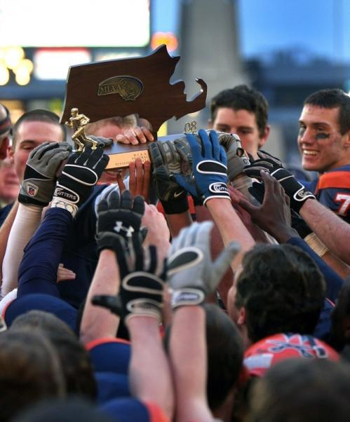 Walpole players all want to get a hand on the Super Bowl trophy.