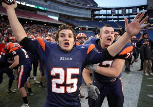 Walpole's Ryan Izzo (25) celebrates with teammate Adam Riegel as time expires.