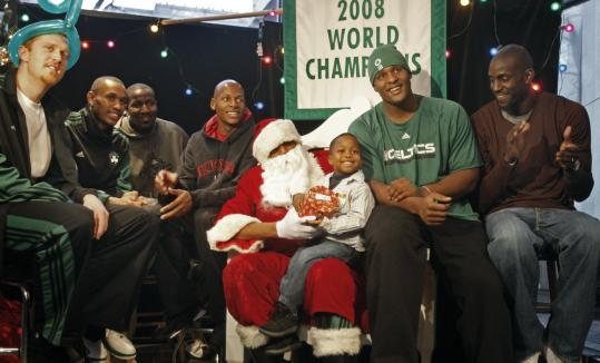Five-year-old Frank Berry of Boston is happy to be sitting on Santa's lap surrounded by Celtics players (from left) Brian Scalabrine, Gabe Pruitt, Kendrick Perkins, Ray Allen, Glen Davis, and Kevin Garnett.