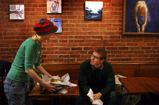 Giocchina Viaggio clears a table at Java Jo's in Jamaica Plain for Michael Young. Owner Vance Welch says they have seen business increase a bit.