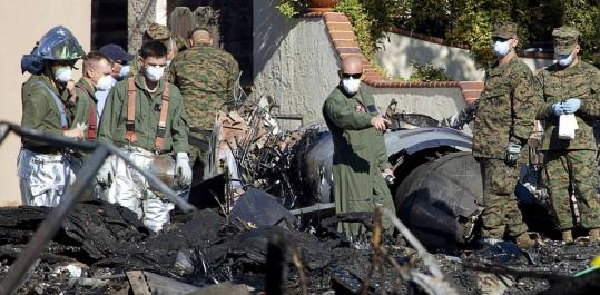 Officials searched debris yesterday near the remains of an F/A-18D fighter jet that crashed in the University City neighborhood of San Diego on Monday. The plane destroyed two houses and killed four members of a family. Several other houses were damaged.