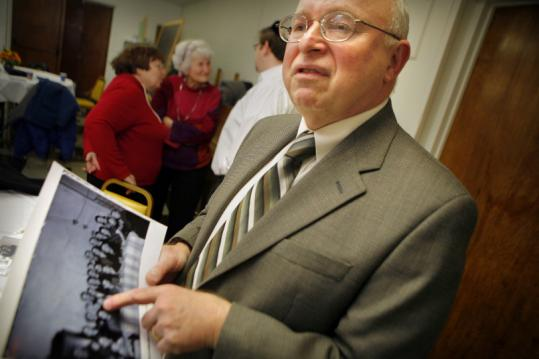 Fred Feldman showed a photograph of himself and his family in Europe after World War II, at Temple Emanu-El in Haverhill.