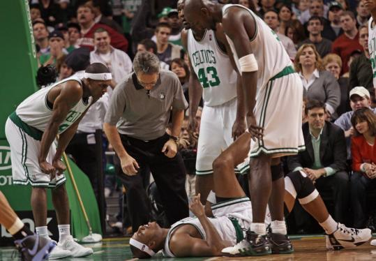Paul Pierce is attended to by teammates (from left) Rajon Rondo, Kendrick Perkins, and Kevin Garnett after his knee buckled near the end of the game. Pierce said the injury didn't appear serious.