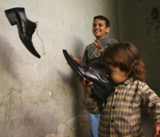 Children played with shoes owned by Iraqi journalist Muntadar al-Zeidi outside his apartment in Baghdad on Monday. Zeidi threw his shoes at President Bush during a press conference in Baghdad on Sunday.