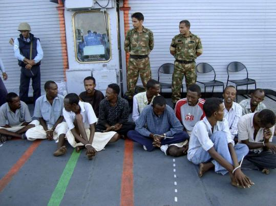 Indian Navy sailors escorted 12 suspected Somali pirates, caught in the Gulf of Aden last week, before handing them over to Yemeni officials yesterday. A large arms cache was also seized.
