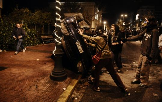Protesters overturned a car yesterday in Athens. The capital was reeling as a protest march sparked more fighting.