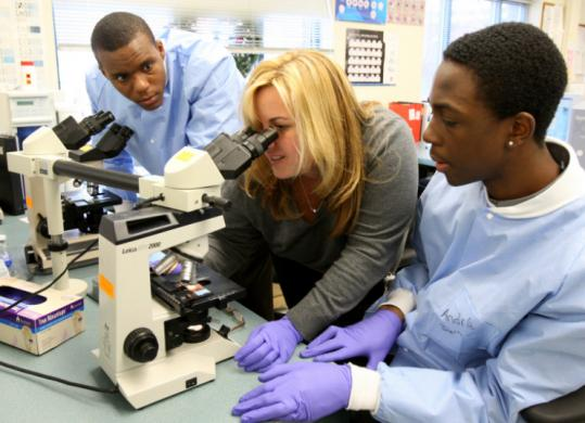 Christine Schromm (center) works with students Tonnie Griham and Andre Lawrence at Codman Square Health Center.