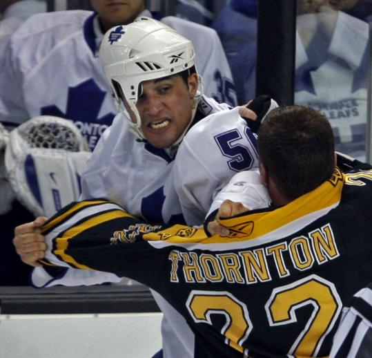Andre Deveaux's helmet may be askew, but the Leaf retains focus on Bruin Shawn Thornton during their first-period fight.