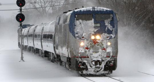 PHOTOS BY JOHN BLANDING/GLOBE STAFFSnow flew yesterday as Amtrak's Downeaster train pulled into the Anderson Regional Transportation Center in Woburn.