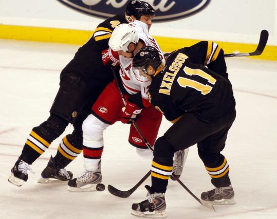 Mark Stuart and P.J. Axelsson double team the Hurricanes' Eric Staal trying to get the puck.