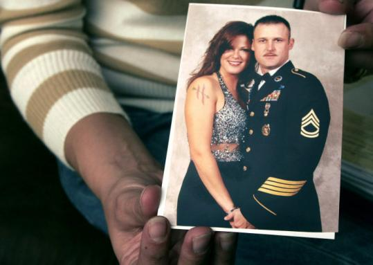 Amanda Henderson displayed a photo of her husband, Sergeant Patrick Henderson, who hanged himself in his shed.