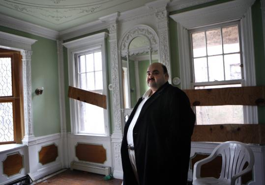 Real estate investor Christ Stamatos in the vandalized Roxbury apartment building recently bought by his family business.