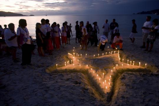 Tourists and others lit candles during a service to remember tsunami victims at a beach in Phuket, Thailand, yesterday.