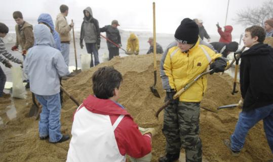 Jeff Koehl (foreground), an assistant leader of Boy Scout Troop 56, helped scout Jack Lindberg, 13, fill sandbags outside the Campton Township Highway Department in Lily Lak