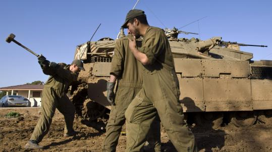Israeli soldiers prepared their tank for battle yesterday as the military began to assemble at the Gaza border.