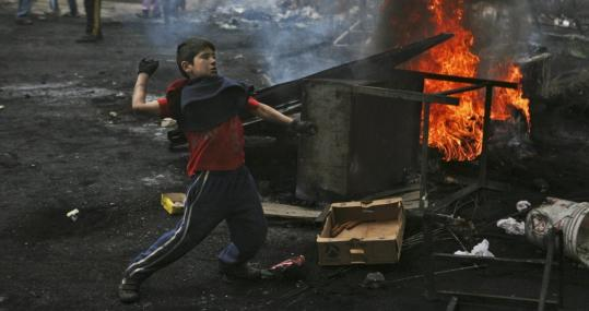 A young Palestinian tossed stones yesterday during clashes with Israeli troops (not seen) at a demonstration against Israel's military operation in Gaza, in the Shuafat refugee camp on the outskirts of Jerusalem.