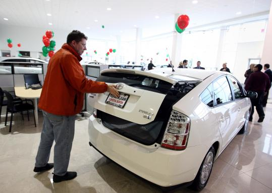 James Jensen checks out a 2009 Prius hybrid while car shopping at Tufankjian Toyota of Braintree earlier this month.