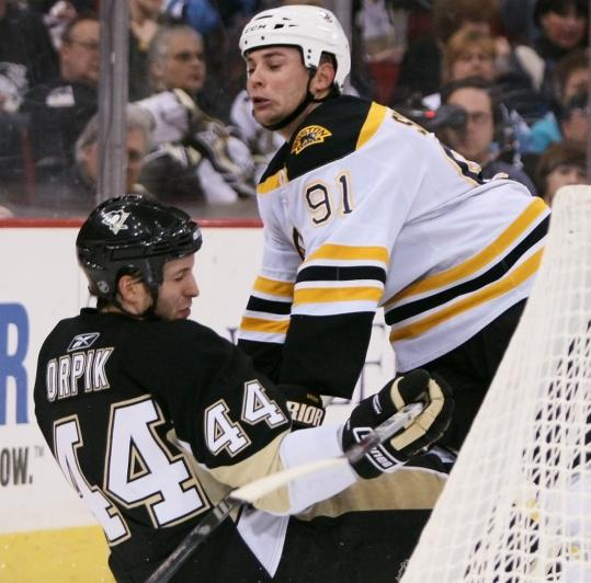 Marc Savard, who had a goal and two assists, checks in with Pittsburgh's Brooks Orpik in the second period.