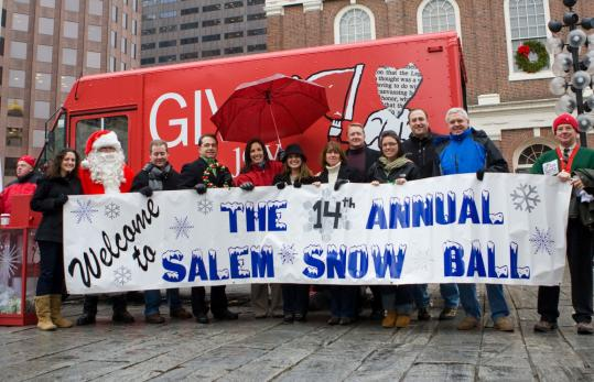 PHOTOS BY TASLIM SIDI FOR THE BOSTON GLOBEThis year's Salem Snow Ball raised $9,500 for Globe Santa. Representatives of the event marched with a giant banner to present Santa with the check at Faneuil Hall last month.